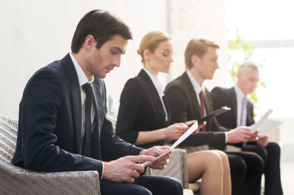 Job candidates. Four people in formalwear waiting in line while sitting at the chairs and holding papers in their hands